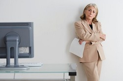 Business woman standing by a computer